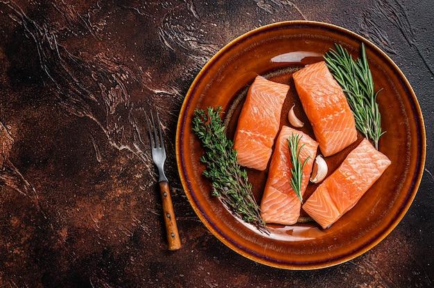 Filetto di pesce salmone crudo fresco bistecche su piatto rustico con timo e rosmarino. sfondo scuro. vista dall'alto. copia spazio.