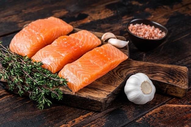 Bistecche di filetto di pesce salmone crudo fresco su tavola di legno con timo. fondo in legno scuro. vista dall'alto.
