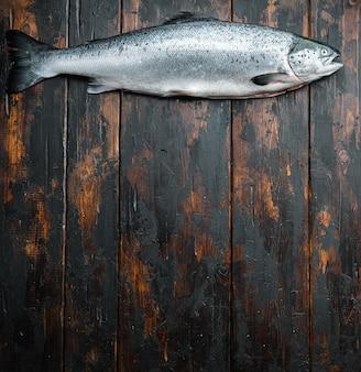 Pesce rosso salmone crudo fresco su fondo di legno, vista dall'alto.