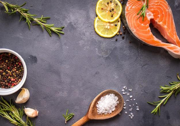 Trancio di salmone crudo fresco, limone, erbe aromatiche, spezie, cucchiaio di legno su fondo di cemento rustico scuro.