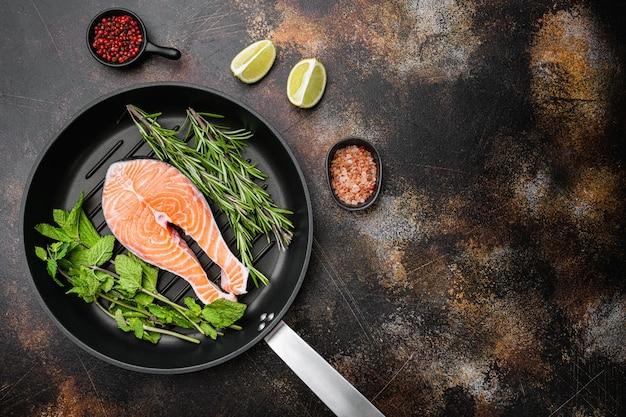 Set di bistecca di salmone crudo fresco, in padella in ghisa, sul vecchio sfondo rustico scuro della tavola, vista dall'alto piatta, con copia spazio per il testo