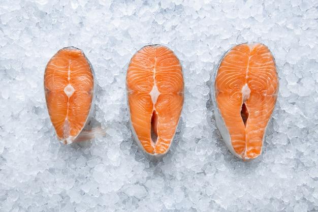 Filetto di salmone crudo fresco tre su ghiaccio da vicino, pesce freddo dall'oceano, cucina a casa e in vista dall'alto del ristorante
