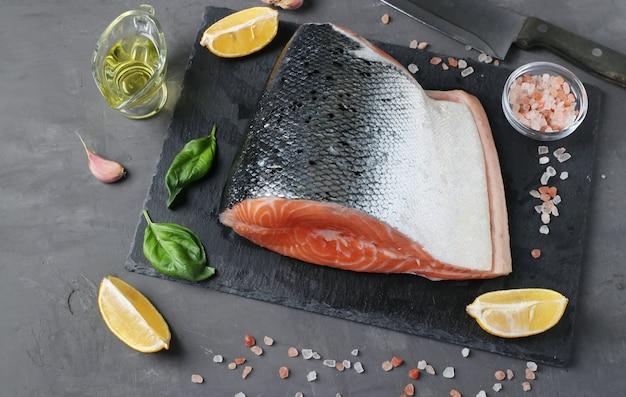 Salmone crudo fresco con ingredienti su tavola di ardesia su sfondo scuro. avvicinamento. vista dall'alto