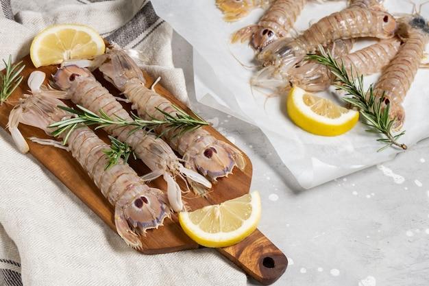 Frutti di mare crudi freschi gamberetti mantide grandi con limone su uno sfondo grigio cemento. ingredienti in un negozio o in un ristorante di pesce, sfondo per un menu di pesce