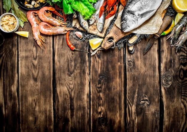 Pesce crudo fresco. una varietà di frutti di mare sulla rete da pesca sul tavolo di legno.