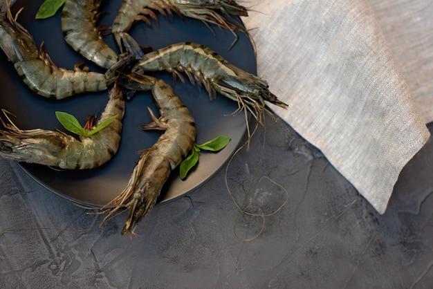 Gamberetti crudi freschi su una banda nera. i frutti di mare sani sono una fonte di proteine. disteso. copia spazio.
