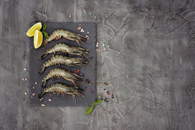 Gamberetti crudi freschi con calce e spezie su una tavola di pietra. i frutti di mare sani sono una fonte di proteine. disteso. copia spazio.
