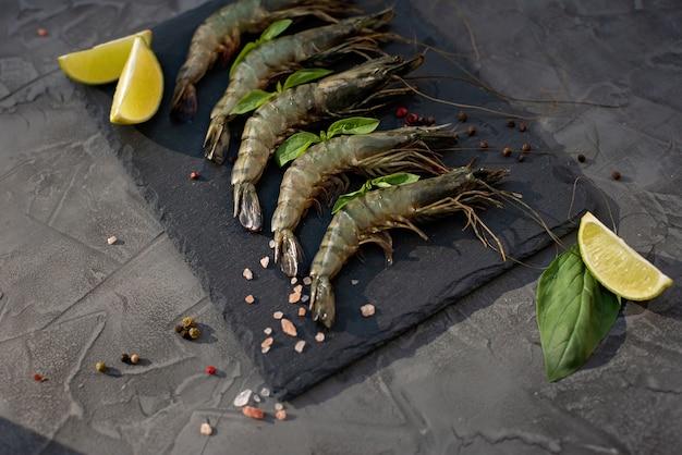 Gamberetti crudi freschi con calce e spezie su una tavola di pietra. i frutti di mare sani sono una fonte di proteine. disteso.