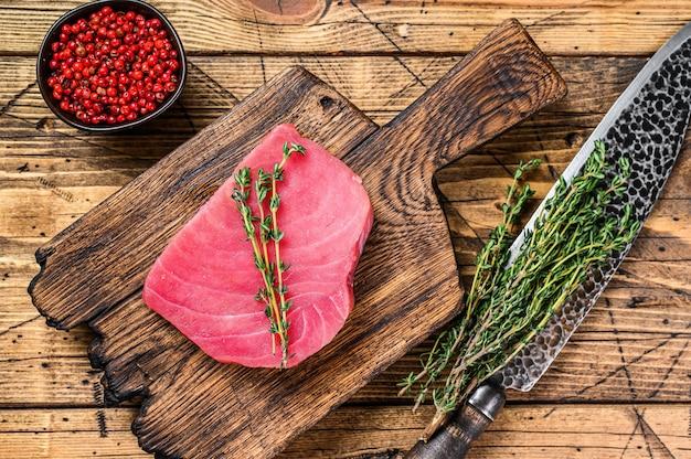 Bistecca di tonno crudo fresco su un tagliere di legno con coltello.