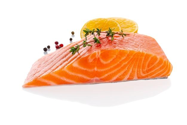 Bistecca di filetto di salmone crudo fresco crudo isolato su priorità bassa bianca con condimento e limone, vista laterale
