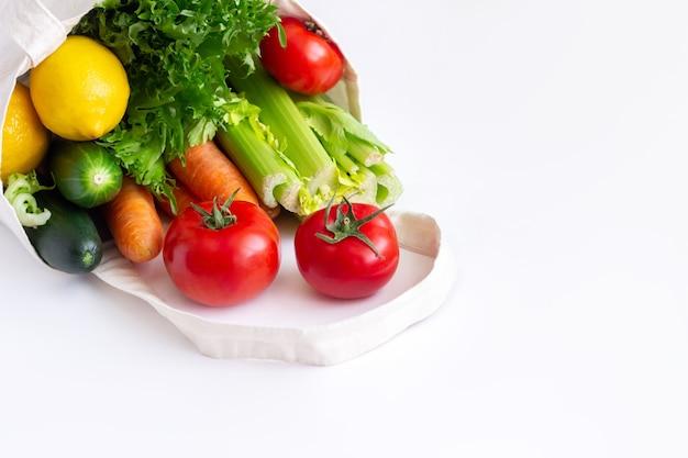 Verdure crude fresche e frutta in un sacchetto di lino riutilizzabile ecologico naturale in tessuto isolato su una superficie bianca