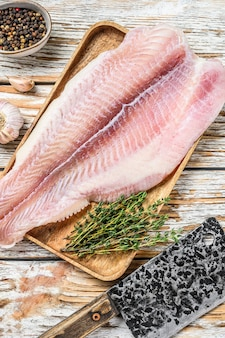 Pesce gatto di filetto di pesce bianco crudo fresco con spezie. fondo in legno bianco. vista dall'alto.