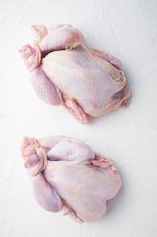 Intera carcassa di pollo cruda fresca, sul tavolo bianco, vista dall'alto