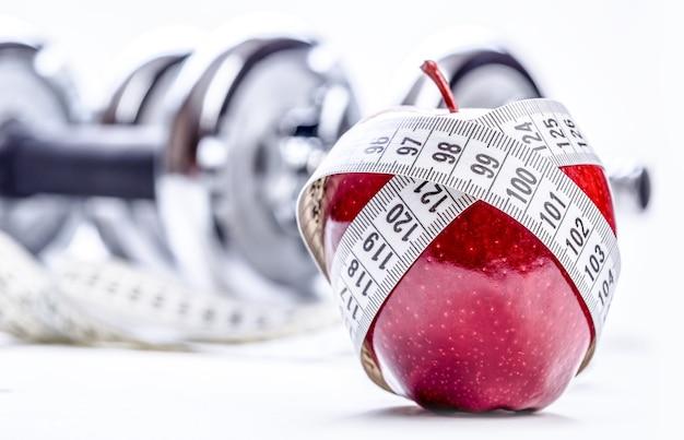 Mela rossa fresca, metro a nastro e in sottofondo manubri fitness. stile di vita sano dieta ed esercizio fisico. colpo dello studio.
