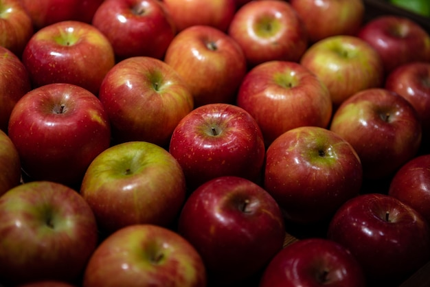 Mele rosse fresche sul bancone del mercato. mele nella scatola di cartone sullo scaffale della drogheria. vista ravvicinata della frutta nel supermercato. alimentazione sana e vegetarianismo