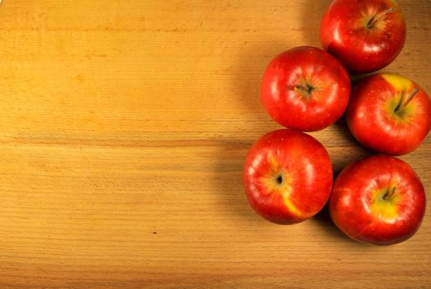 Mele rosse fresche sui precedenti di legno