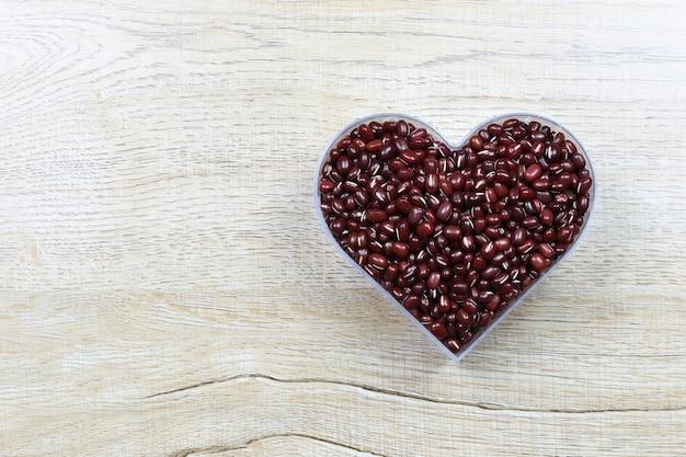 Il fagiolo rosso fresco in uno stampo a forma di cuore poggia su un tavolo di legno e ha uno spazio per il design in amore e il giorno di san valentino.