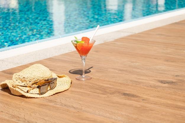 Cocktail rosso fresco con ghiaccio in vetro, cappello da spiaggia e occhiali da sole sulla piscina. succo tropicale per vacanze di lusso. concetto di vacanza estiva e viaggi. foto di alta qualità