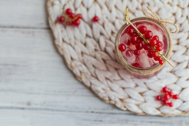 Cocktail di ribes rosso fresco in un barattolo di vetro. cocktail rosa estivo con ribes rosso e cubetti di ghiaccio sulla tavola di legno bianca