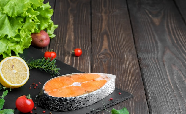 Trancio di pesce rosso fresco su una tavola di legno scura con le verdure