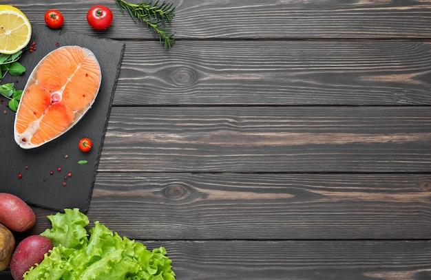 Trancio di pesce rosso fresco, salmone su una tavola di legno scura