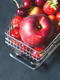 Carrello fresco del supermercato delle bacche della frutta rossa sul nero