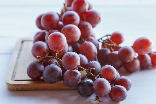 Frutta fresca dell'uva rossa sulla tavola di legno
