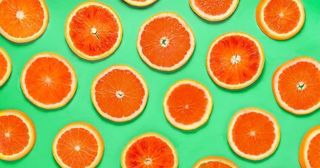 Fette di agrumi di arancia rossa fresca modellata su sfondo verde. direttamente sopra.