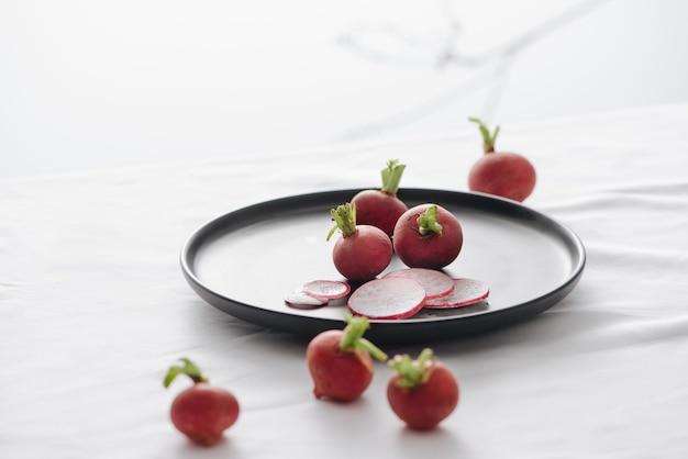 Ravanelli rossi freschi con gambo e radici in un piatto nero sul tavolo