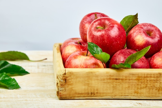 Frutti maturi rossi freschi delle mele nella scatola di legno Foto Premium