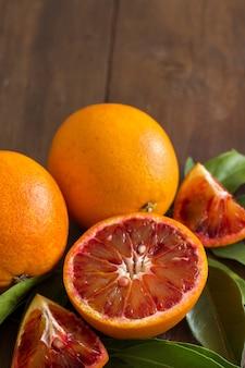 Arance siciliane rosse fresche con foglie su un tavolo di legno