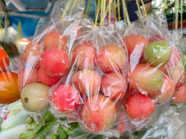 Pomodori rossi freschi confezionati in sacchetti di plastica pronti per la vendita nel mercato di strada.