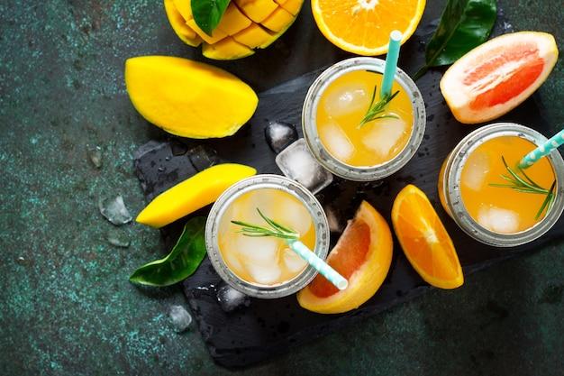 Bevande estive fresche e rinfrescanti bevande multifrutta di agrumi e mango con ghiaccio copia spazio