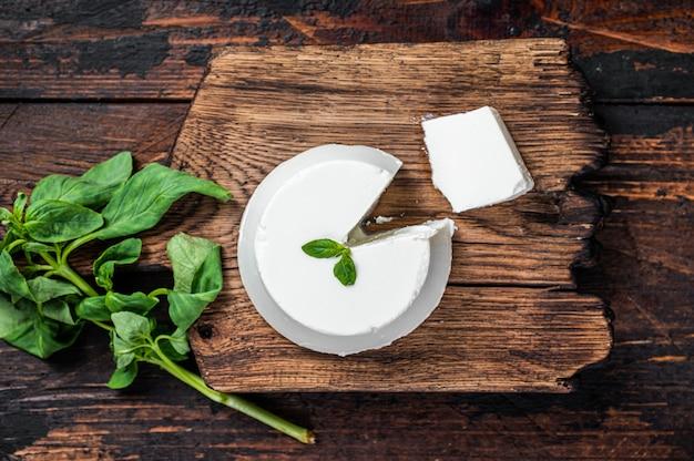 Crema di ricotta fresca su tavola di legno con basilico.