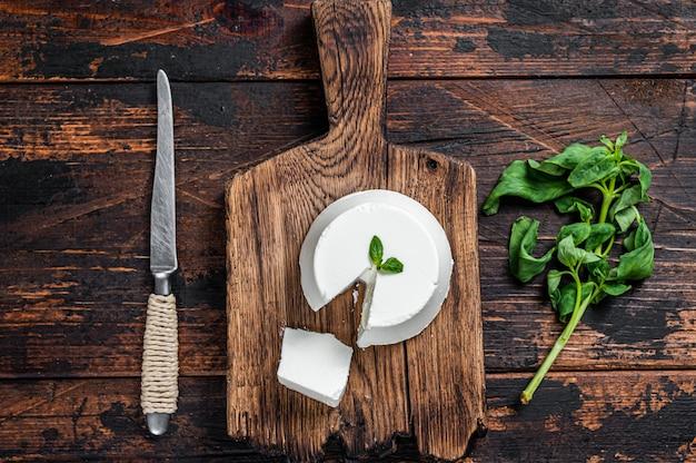 Crema di ricotta fresca su tavola di legno con basilico