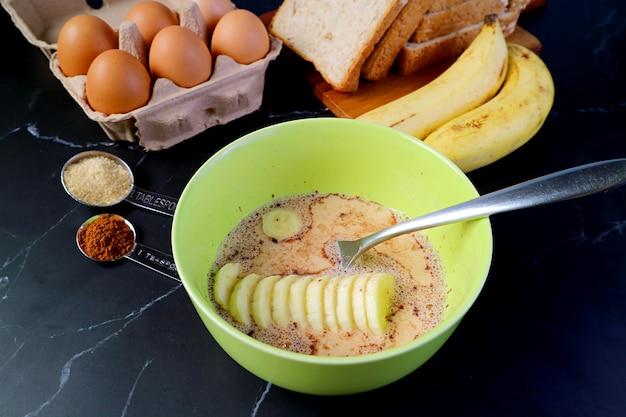 Banana fresca matura aggiunta nella miscela per cuocere il budino di pane alla banana fatto in casa