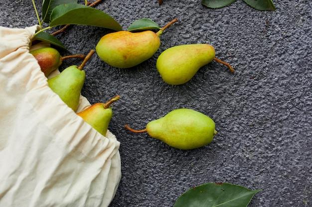 Pere fresche di frutta matura in una borsa ecologica riutilizzabile per la spesa su uno sfondo scuro, concetto di drogheria, piatto, ecologico, raccolto autunnale. copia spazio.
