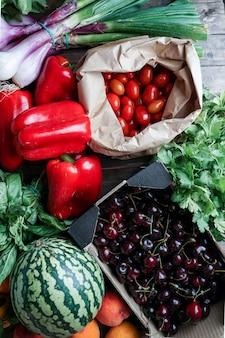 Frutta e verdura fresca e matura in confezione di carta ecologica, ciliegia, pepe, anguria, pomodorini, erbe aromatiche