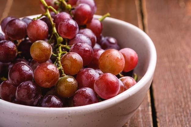 Bacche mature fresche dell'uva in ciotola su legno marrone, macro di vista di angolo