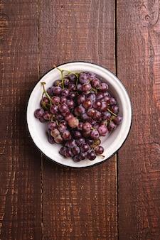 Bacche mature fresche dell'uva in ciotola su legno marrone