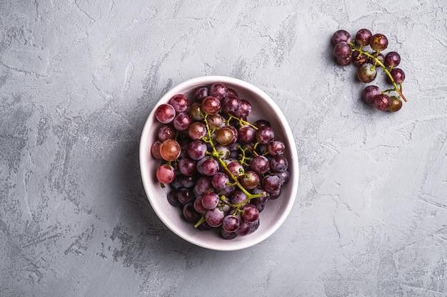 Bacche fresche dell'uva matura nella ciotola su calcestruzzo di pietra