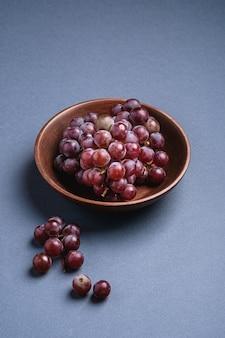 Bacche mature fresche dell'uva in ciotola di legno marrone su fondo minimo grigio blu, vista di angolo