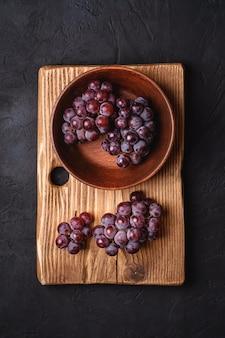 Bacche fresche dell'uva matura in ciotola di legno marrone e tagliere su fondo di pietra scuro, vista dall'alto