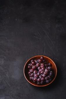 Bacche fresche dell'uva matura in ciotola di legno marrone sulla superficie di pietra scura