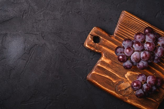 Bacche mature fresche dell'uva sul tagliere di legno marrone su fondo di pietra scuro, spazio della copia di vista superiore