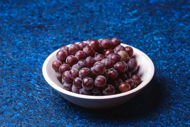 Bacche fresche dell'uva matura in ciotola di legno bianca su fondo astratto blu, vista di angolo