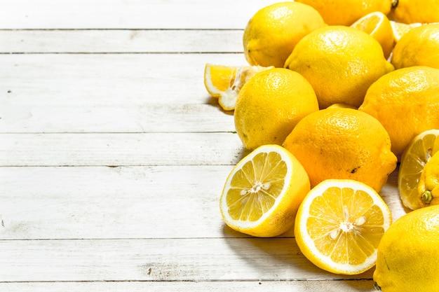 Limoni maturi freschi. su un tavolo di legno bianco.