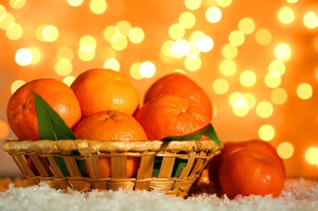 Mandarini maturi freschi sulla neve, sulla superficie delle luci