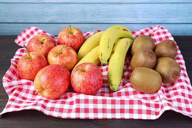 Frutti nutrienti maturi freschi su un vassoio con vestiti a scacchi sul tavolo rustico in legno