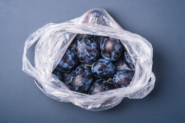 Frutti di prugna freschi maturi nel pacchetto del sacchetto di plastica su sfondo grigio blu minimo, vista dall'alto